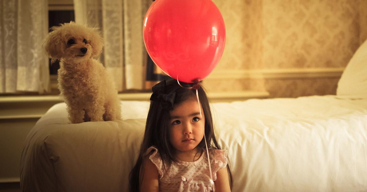 Petite fille avec un caniche et un ballon
