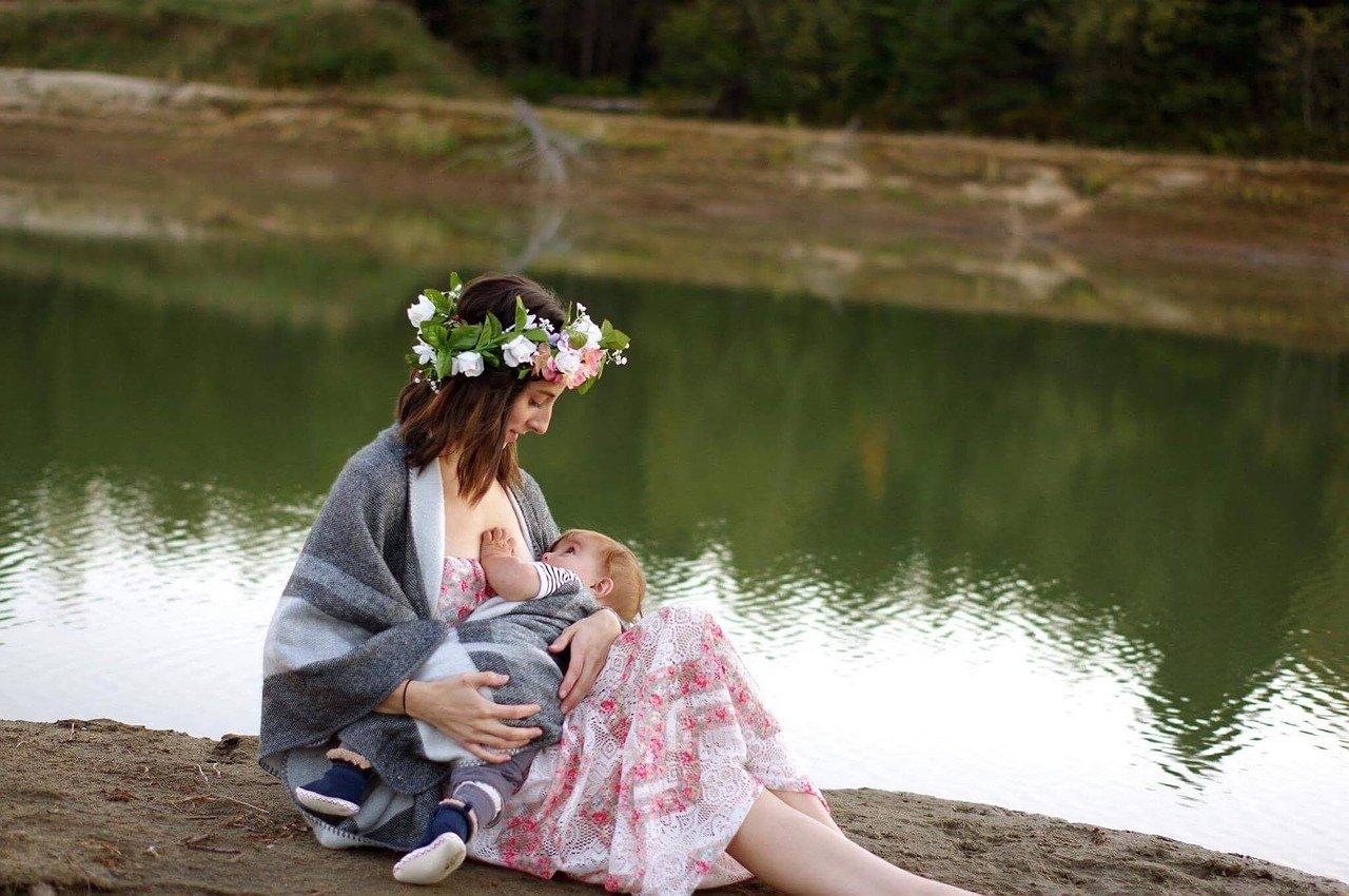 Maman qui allaite à l'extérieur avec son bébé dans les bras
