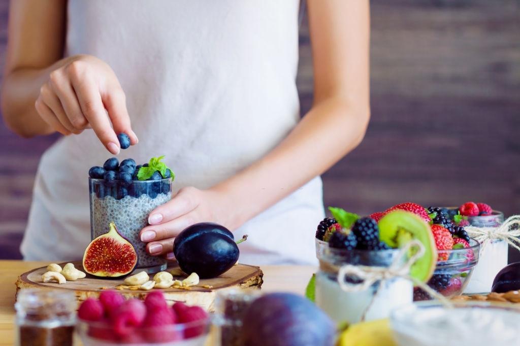 Femme enceinte prépare un yaourt sain avec des fruits frais